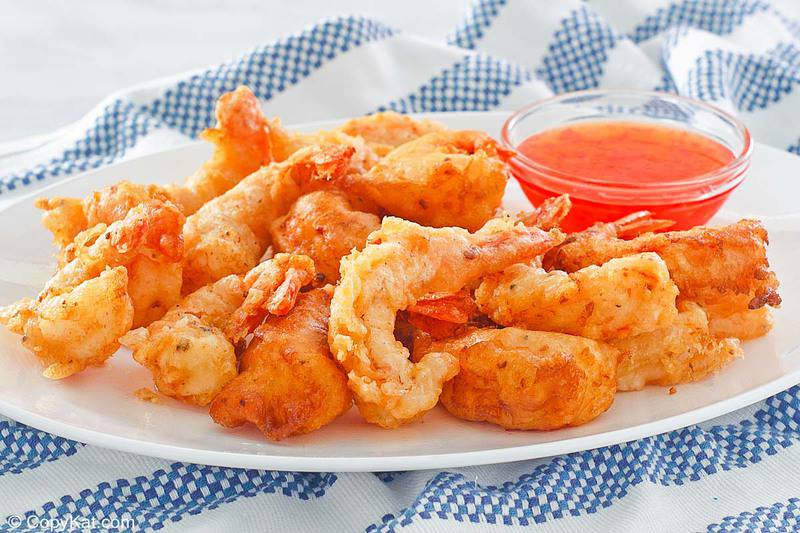 beer battered shrimp and dipping sauce on a plate
