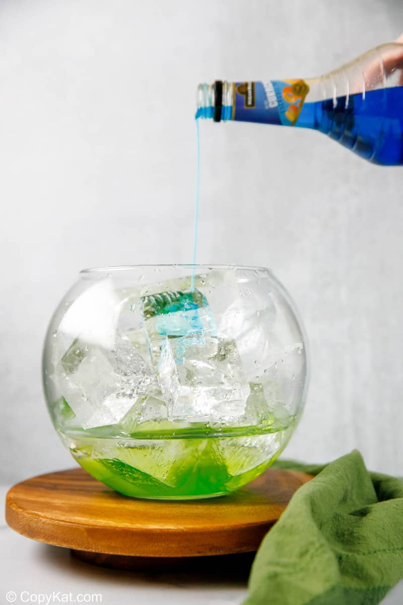 pouring blue curacao into a glass