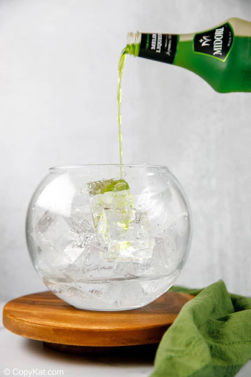 pouring Midori melon liqueur into a glass