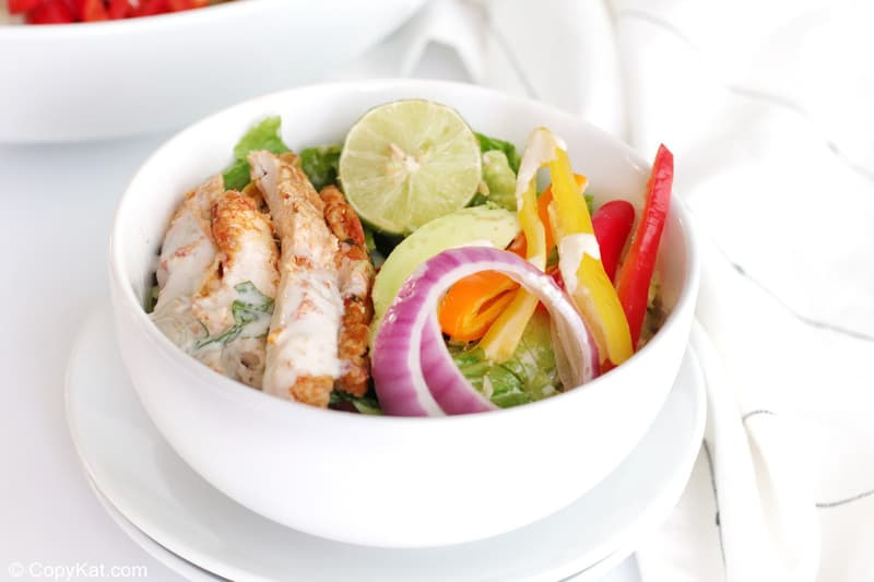 chicken fajita salad in a bowl on top of plates