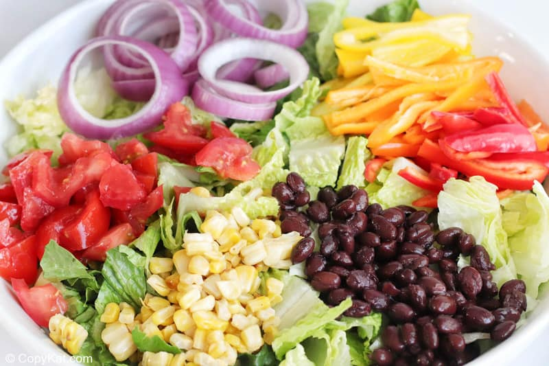 romaine, tomatoes, onions, peppers, corn, and black beans in a bowl