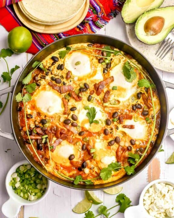 huevos rancheros in a pan, corn tortillas, avocado, and cojita cheese