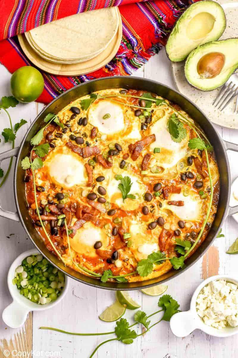 huevos rancheros in a pan, corn tortillas, avocado, and cojita cheese