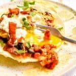 fork breaking the egg yolk on huevos rancheros