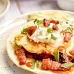 huevos rancheros topped with crema fresca and bacon