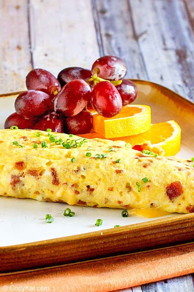 bacon and cheese omelette and fruit on a plate