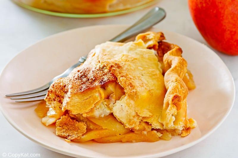 Una rebanada de tarta de manzana a la antigua y un tenedor en un plato