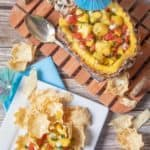 pineapple mango salsa in a pineapple and on tortilla chips