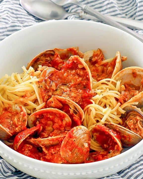 red clam sauce, clams, and pasta in a bowl