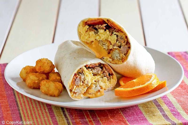 meat and cheese breakfast burrito and tater tots on a plate