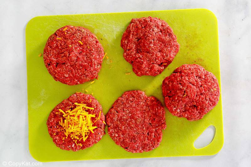 ground beef patties and shredded cheddar cheese on top of one of them