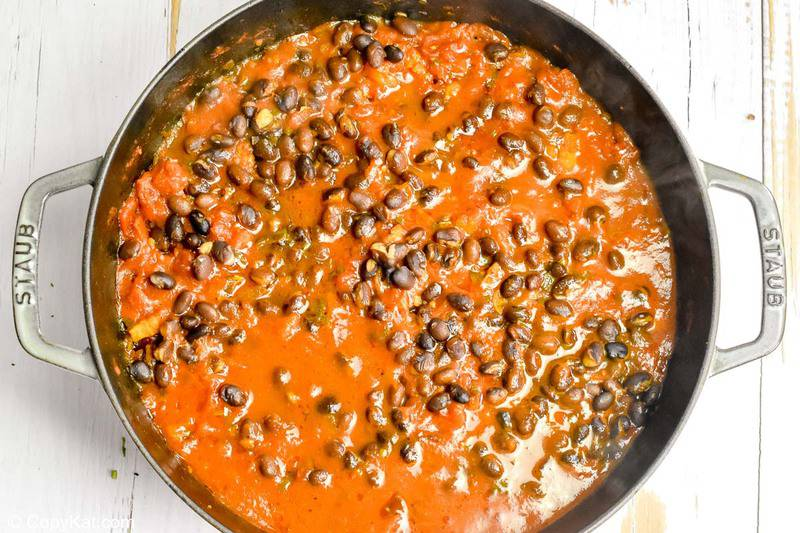 tomato sauce with black beans and bacon for huevos rancheros in a pan