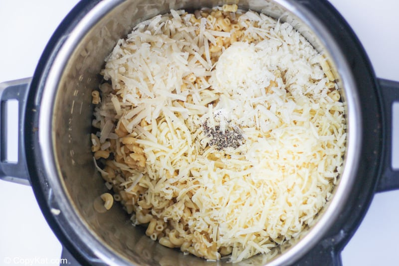 adding cheeses and seasoning to macaroni in an Instant Pot