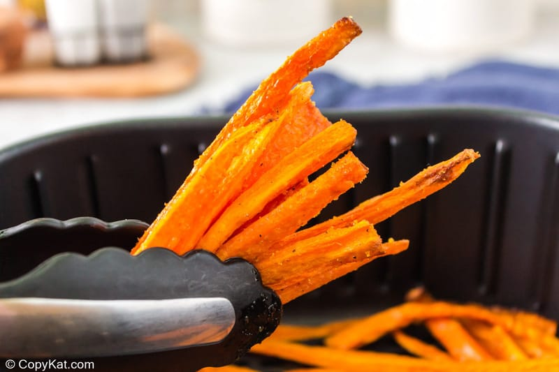 air fried carrot sticks held by tongs