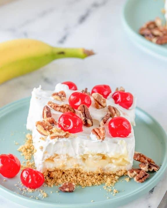 banana split cake slice on a plate next to a banana