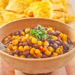 a bowl of black bean and corn salad and corn tortilla chips on a platter