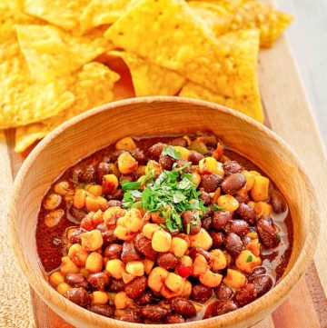 a bowl of black bean and corn salad next to tortilla chips