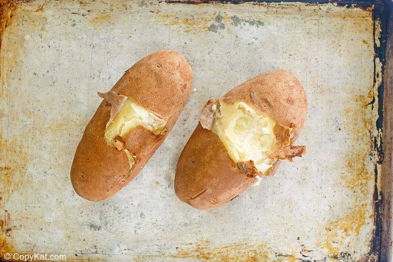 partially peeled boiled russet potatoes on a baking sheet