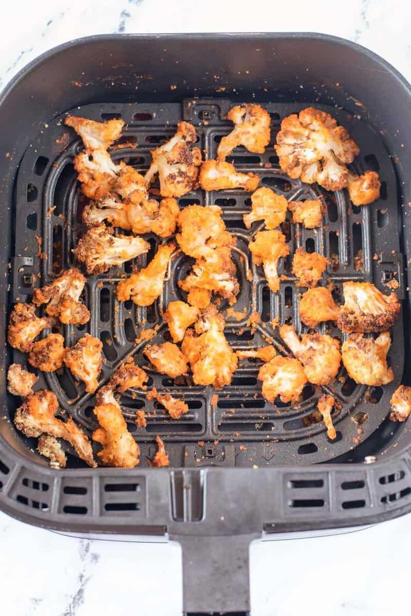 cooked buffalo cauliflower in an air fryer basket