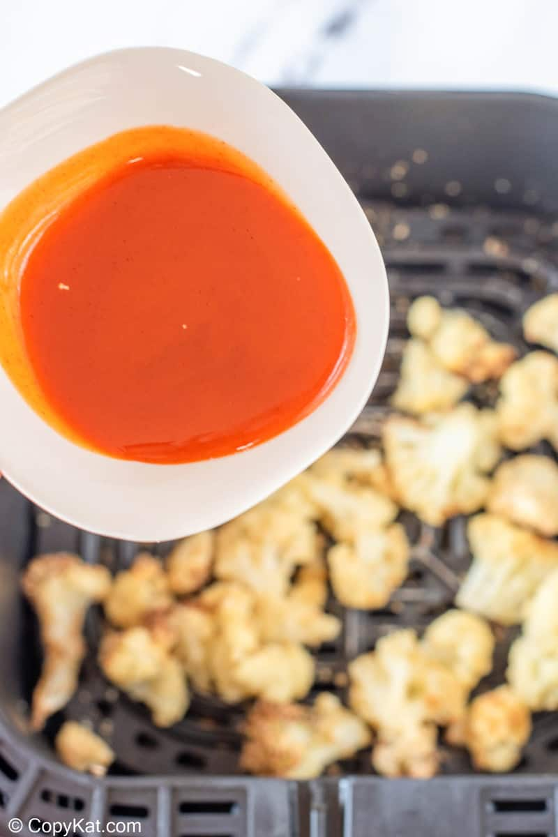 pouring buffalo sauce over cooked cauliflower in an air fryer basket