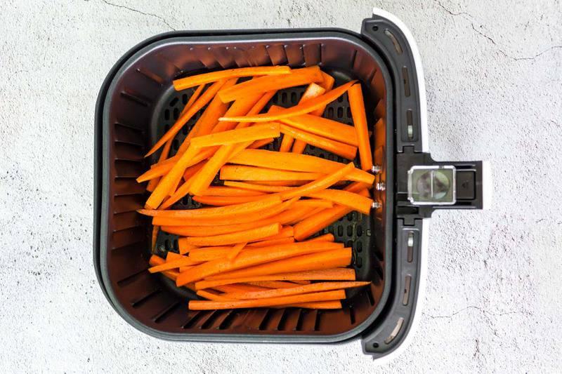 carrot sticks in an air fryer basket