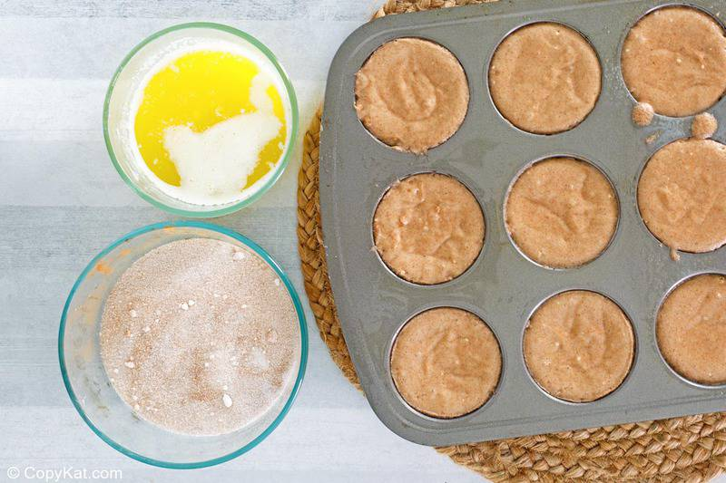 donut muffin batter in a muffin pan, melted butter, and cinnamon sugar mixture