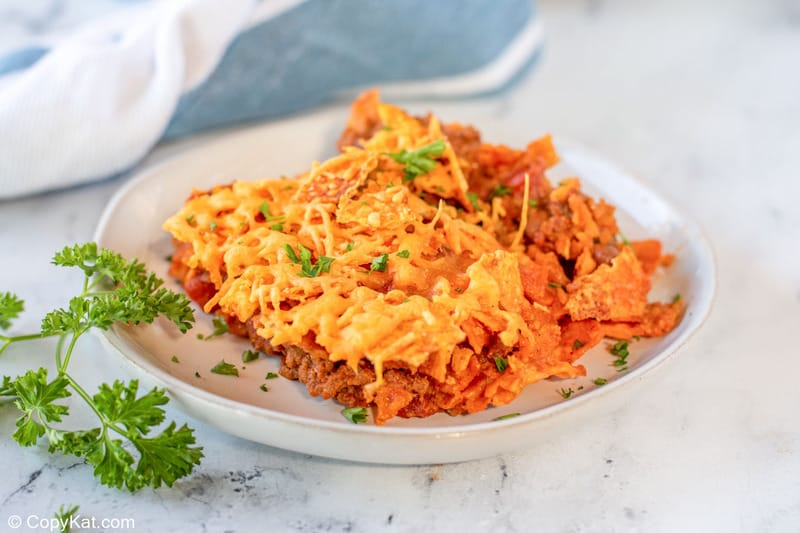 Dorito casserole serving on a plate and some parsley