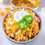 Frito Pie topped with onions, sour cream, and jalapeno pepper slices