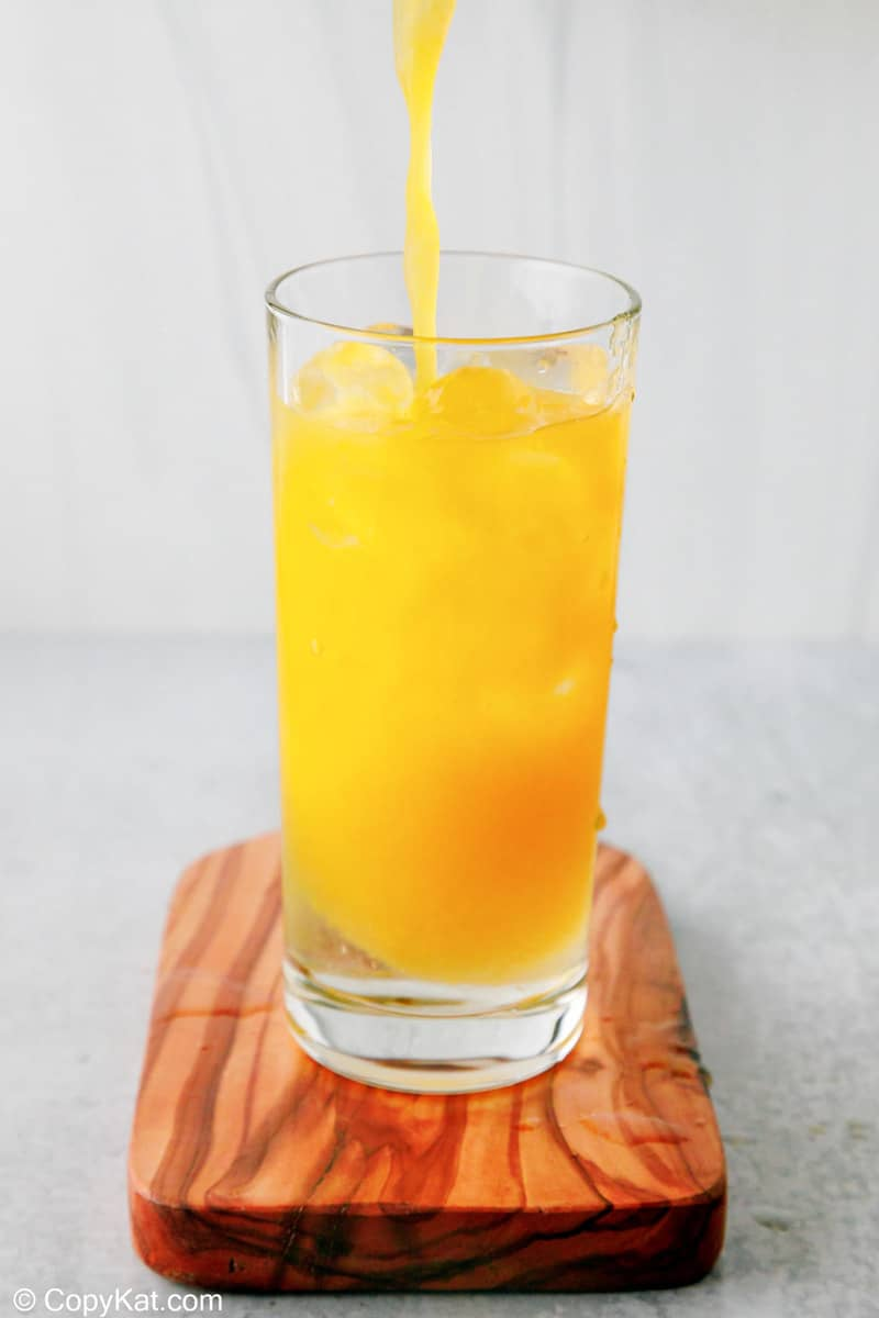 adding orange juice to peach schnapps and ice in a glass
