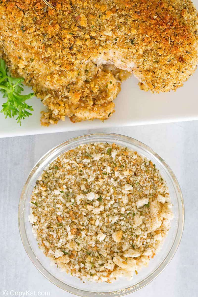 a bowl of homemade Italian seasoned bread crumbs next to breaded chicken