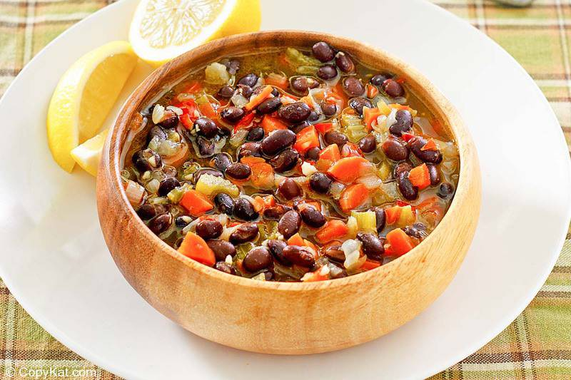 a bowl of homemade Panera black bean soup and lemon slices on a plate