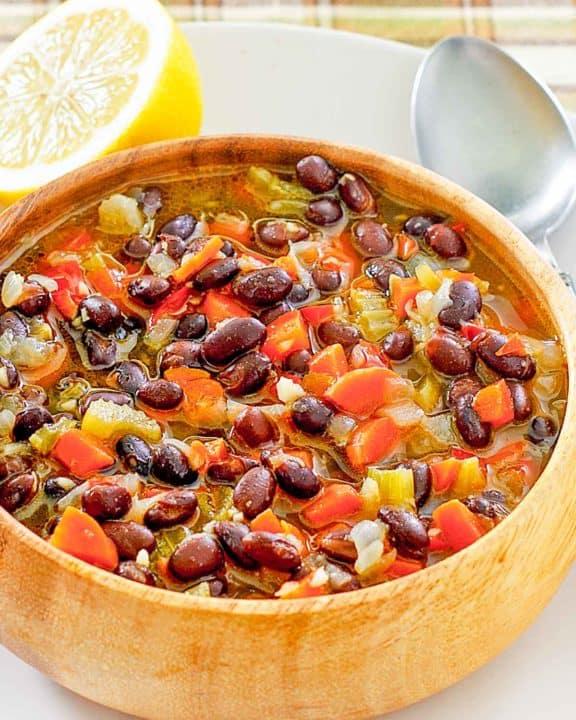 a bowl of homemade Panera black bean soup, a spoon, and half of a lemon