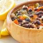a bowl of black bean soup and a lemon