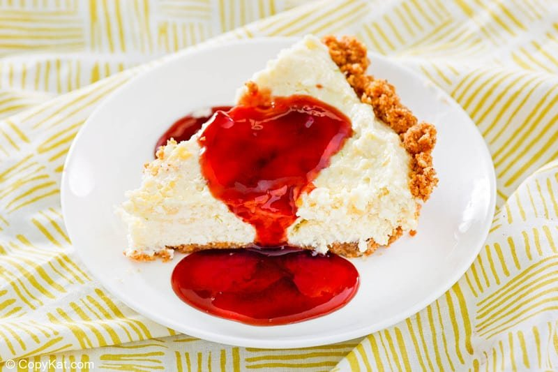 una rebanada de tarta de lima Pappadeaux casera cubierta con salsa de frambuesa