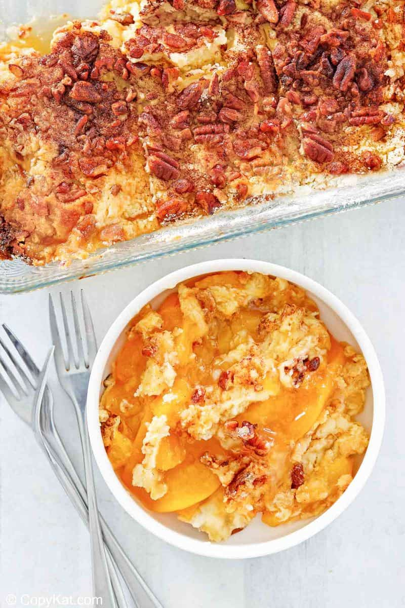 overhead view of peach dump cake in a baking dish and a bowl