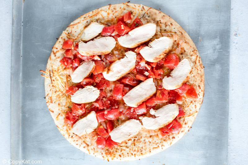 pizza crust topped with tomatoes and chicken