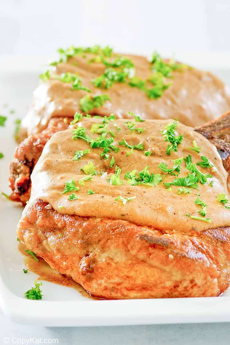 two fried pork chops with gravy