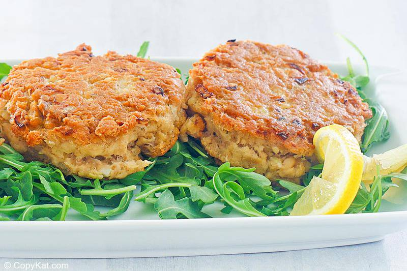 two salmon patties, lemon slice, and arugula on a plate