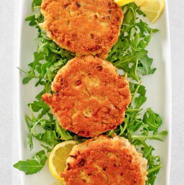 three salmon patties, lemon slices, and arugula on a platter