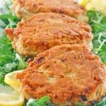 salmon patties, lemon slices, and arugula on a platter