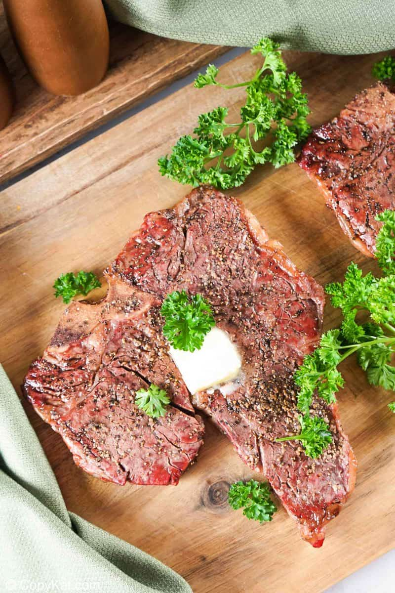smoked steak and fresh parsley on a wood board