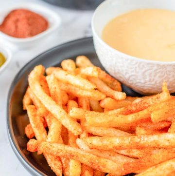 homemade Taco Bell Nacho Fries and cheese sauce on a plate