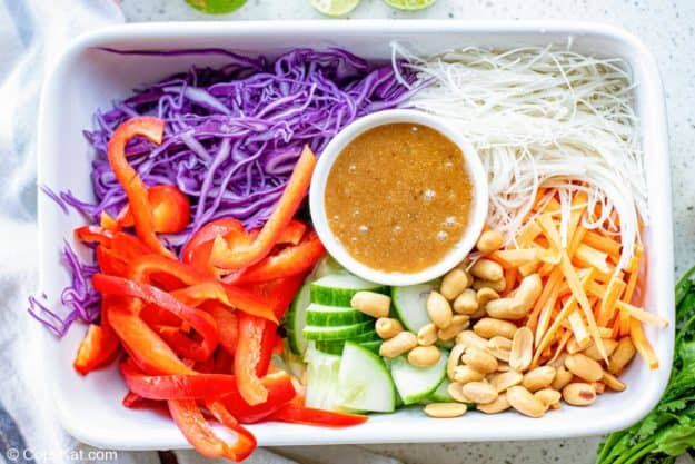 Thai noodle salad ingredients and dressing in a rectangular dish