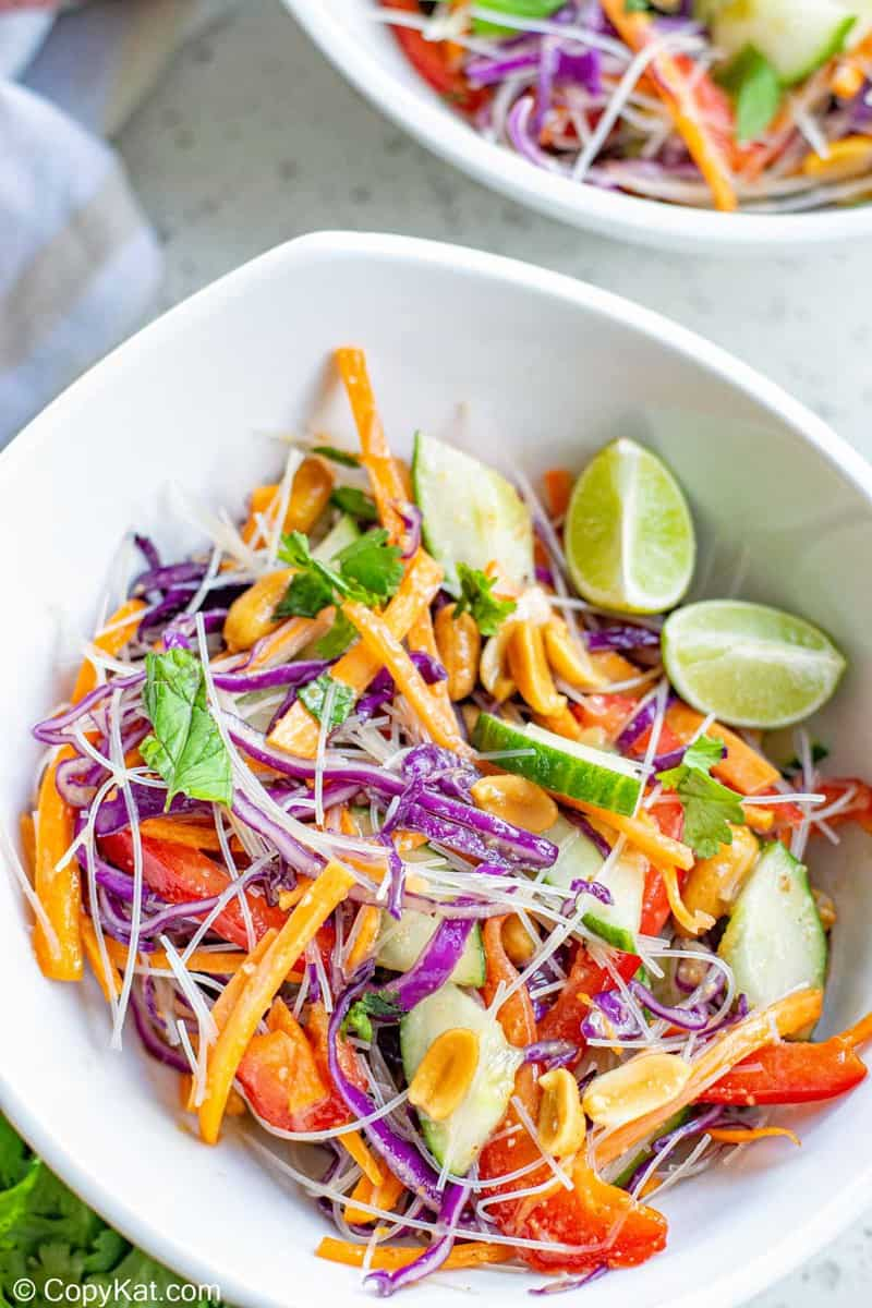 Thai noodle salad and lime wedges in a bowl