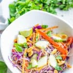 Thai noodle salad in a bowl and Thai basil behind it