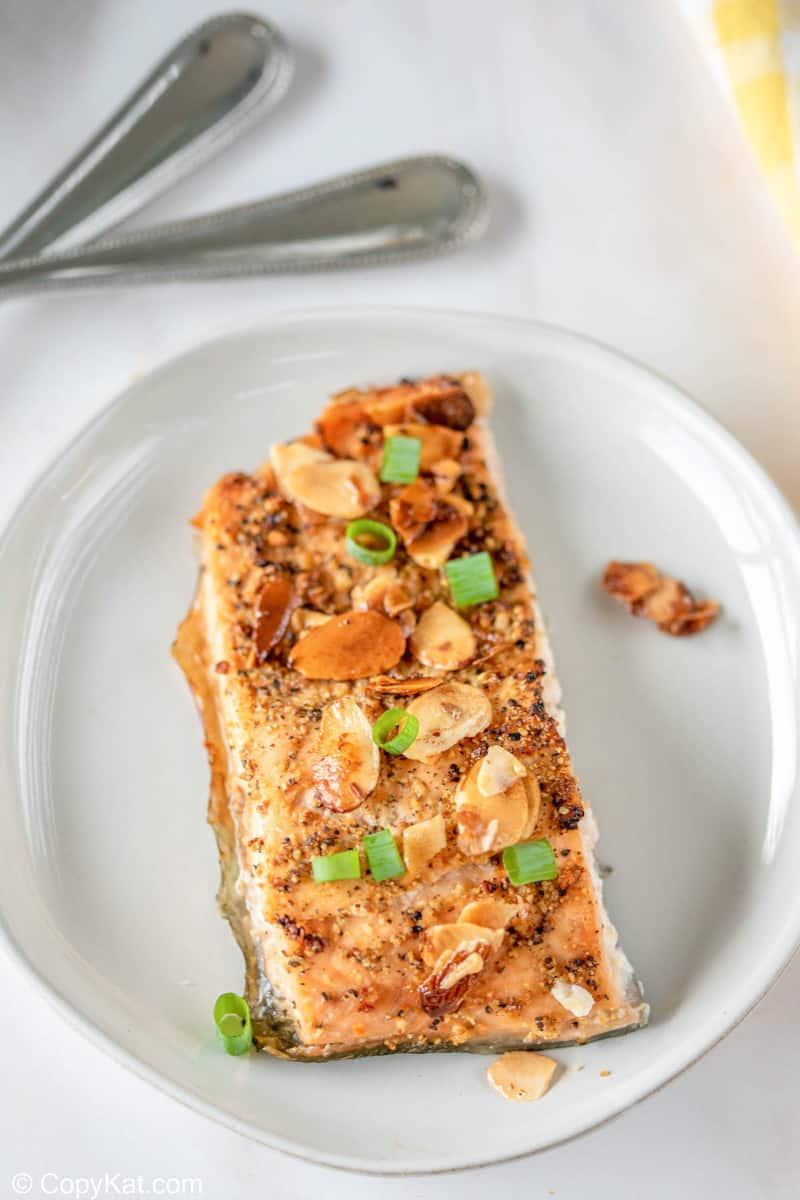 air fried salmon almondine on a white plate