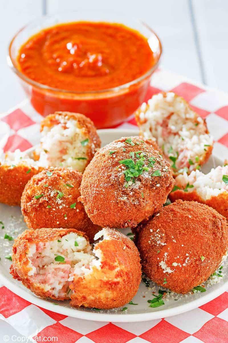 Arancini Italian Rice Balls on a plate and a bowl of marinara sauce