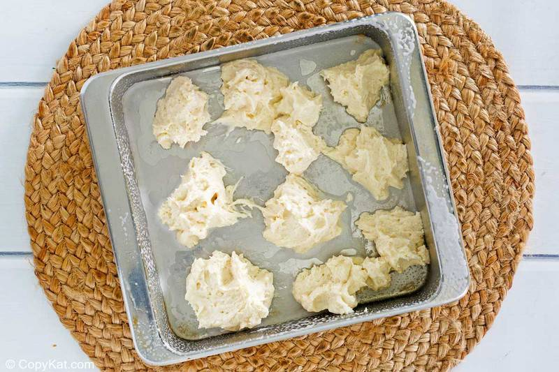 spoonfuls of dough for Bisquick apple cobbler in a baking dish