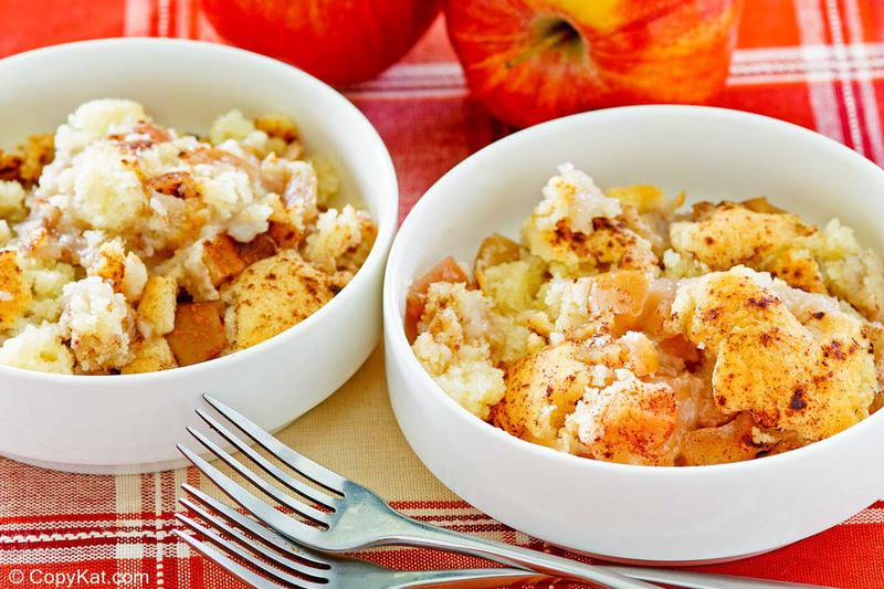 two bowls of Bisquick apple cobbler, two forks, and two apples