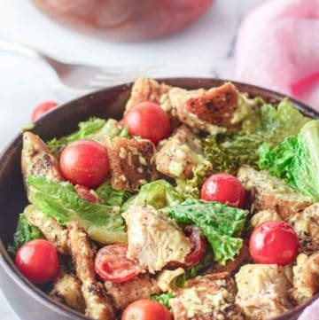 chicken Caesar salad and cherry tomatoes in wood bowls